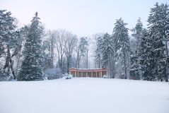 Small colonnade arbor in wintertime. Small colonnade arbor in snowy winter forest park Royalty Free Stock Photo