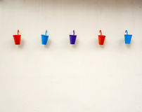 Small color buckets on wall background Royalty Free Stock Images