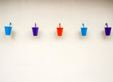 Small color buckets on wall background Royalty Free Stock Photo
