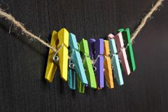 Small colored clothespins on a rope. On black background Royalty Free Stock Photography