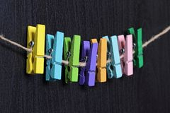 Small colored clothespins on a rope. On black background Royalty Free Stock Images