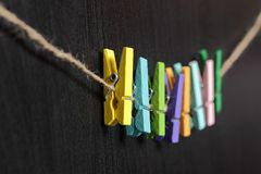 Small colored clothespins on a rope. On black background Stock Photos