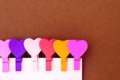 Small colored hearts hold a paper note. The concept of a note to royalty free stock photos