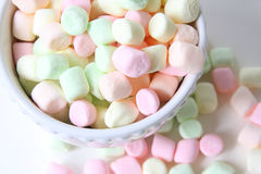 Small colored marshmallows. In white bowl, isolated on white background Royalty Free Stock Photo