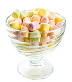 Small colored puffy marshmallows in a glass bowl. Isolated on the white background Royalty Free Stock Photography