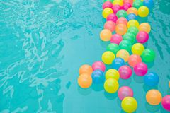 Small colorful beach balls floating in swimming pool abstract concept for pool party s. royalty free stock photos