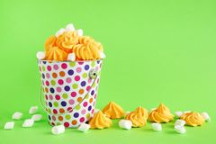 Small colorful bucket filled with yellow meringue and white marshmallows on a green background. stock photos