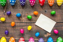 Small colorful easter eggs. Mockup of white piece of paper and small colorful eggs on wooden table with double easter eggs banner Royalty Free Stock Photos