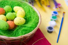Green nest in a basket with small colorful Easter eggs, decoration, close-up easter concept, holiday tradition, blurred paints. Small colorful eggs in a nest stock photo