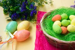 Green nest in a basket with small colorful Easter eggs, decoration, close-up easter concept, holiday tradition, blurred paints. Small colorful eggs in a nest royalty free stock photography