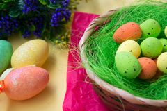 Green nest in a basket with small colorful Easter eggs, decoration, close-up easter concept, holiday tradition, blurred paints. Small colorful eggs in a nest royalty free stock photo