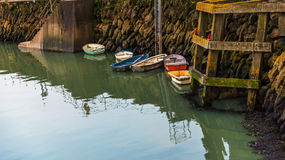 Small colorful fishing boats moored in a small harbor, water sur Royalty Free Stock Photography