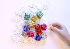Small colorful gift boxes in child& x27; s hands. Christmas and NewYear decorations process. Small colorful gift boxes in child& x27;s hands. Christmas and stock photography