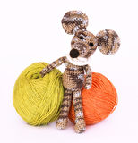 Small colorful knitted toy mouse in a white scarf playing with c Royalty Free Stock Photography