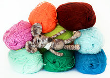Small colorful knitted toy mouse in a white scarf playing with c. Olored yarn, threads of wool, Bright children's toy, clew Royalty Free Stock Photo