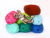Small colorful knitted toy mouse in a white scarf playing with c. Olored yarn, threads of wool, Bright children's toy, clew Royalty Free Stock Image