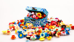 Small, colorful paper flowers in a painted, wooden chest Royalty Free Stock Image