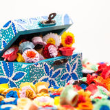 Small, colorful paper flowers in a painted, wooden chest Stock Photo