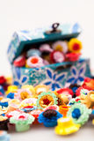 Small, colorful paper flowers in a painted, wooden chest Stock Photography
