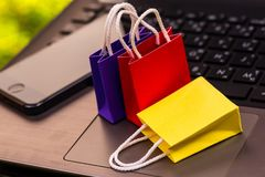 Small colorful paper shopping bags with mobile phone on a laptop royalty free stock photo