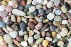 Small colorful pebbles background, simplicity, daylight, stones. Small colorful pebbles background, simplicity, stone in daylight, various colors Royalty Free Stock Image