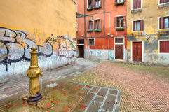 Small colorful plaza. Venice, Italy. Water pump on small plaza among old typical venetian colorful houses and walls with graffiti in Venice, Italy stock photos