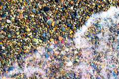 Small colorful wet stones. And water on beach in seacoast Royalty Free Stock Photos