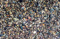 Small colorful wet stones. And water on beach in seacoast Royalty Free Stock Images