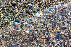Small colorful wet stones. And water on beach in seacoast Stock Images