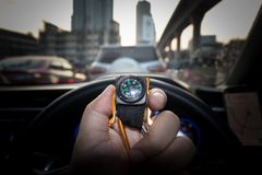 Small compass in man hand. Who is tracking the direction with traffic jam in city Royalty Free Stock Image