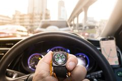 Small compass in man hand. Who is tracking the direction with traffic jam in city Stock Photo