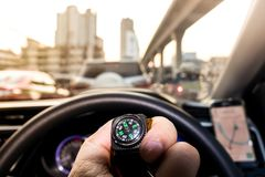 Small compass in man hand. Who is tracking the direction with traffic jam in city Stock Photos