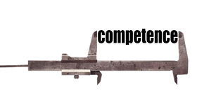 Small competence. Color horizontal shot of a caliper and measuring the word competence royalty free stock photo