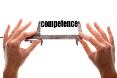 Small competence. Color horizontal shot of two hands holding a caliper and measuring the word competence stock images