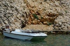 Small concrete molo near steep cliff in small cove with white fisherman motor boat. Adriatic sea, Croatia. Shore near village Vrsi Stock Images