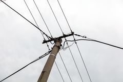 Small concrete pillar with power lines, overcast sky in background. royalty free stock photos