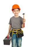 Small constructor kid holding hammer. Small constructor kid boy holding hammer and tools container isolated on white background Stock Photo