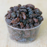 Small Container of Raisins. Closeup of Small Container of Raisins on a Bamboo Board royalty free stock photos