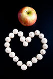 Small cookies laid in the shape of heart and apple on black back Stock Photography