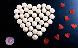 Small cookies laid in the shape of heart with red paper hearts o Stock Image