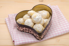 Small cookies in powdered sugar in a tin box in heart shape on c. Small homemade cookies in powdered sugar in a tin box in heart shape on cotton checkered napkin stock photography
