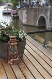 Small copper lantern is on the wooden table with flowers. Near the river in the day Royalty Free Stock Photos