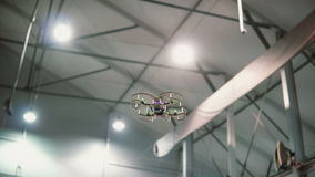 Small copter flies under the ceiling indoors. Drone flying over the floor. stock images