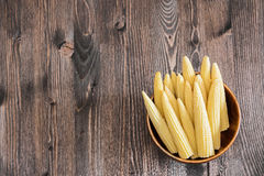 Small corn ears on wooden background. Maize ears on old wooden background with copy space Royalty Free Stock Images