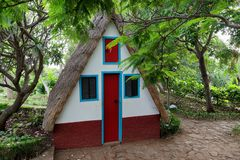 Small cosy chalet with a triangular thatched roof in between of green trees. Portuguese island of Madeira royalty free stock photography
