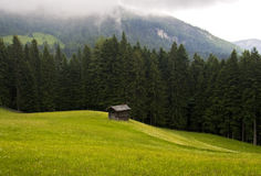 Small Cottage. A small single cottage standing on a hilly green field with a forest and mountains as a backdrop Stock Images