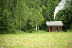 Small cottage. In meadow near forest Royalty Free Stock Photos