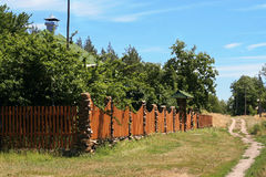 Small cottage in the countryside. Small cottage behind the fence in the countryside Stock Image