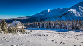 Small cottage at the foot of the mountains in winter Stock Image