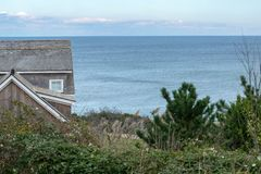 A small cottage, green bushes and shrubs, against the blue horizon inthe background, Block Island, RI, USA stock photo